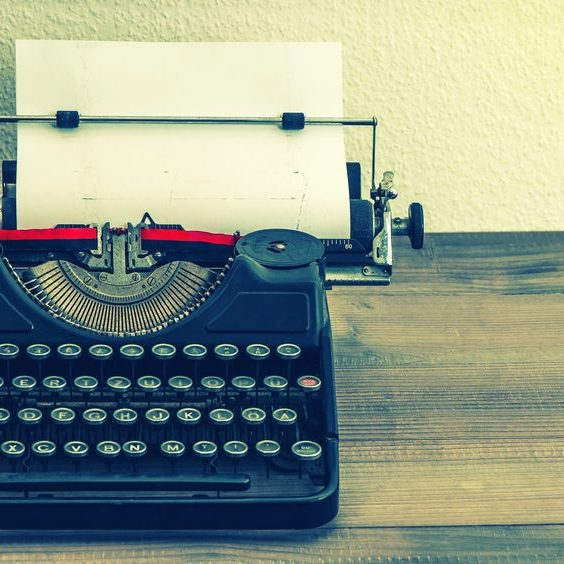 27483115 - retro typewriter with white paper page on wooden table  vintage style toned picture